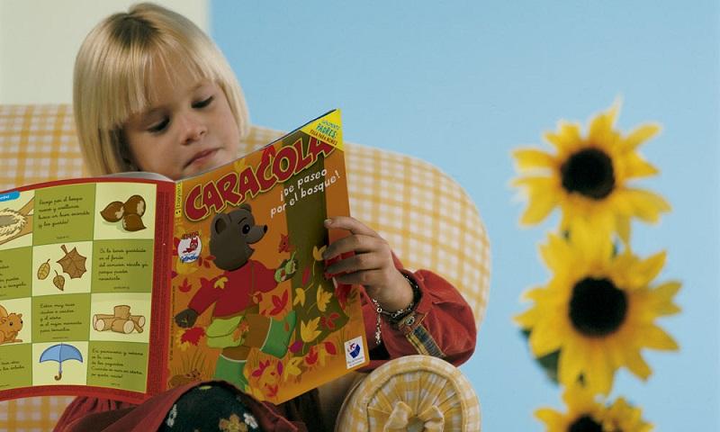 Un niño lee con atención una revista de Bayard Editorial.